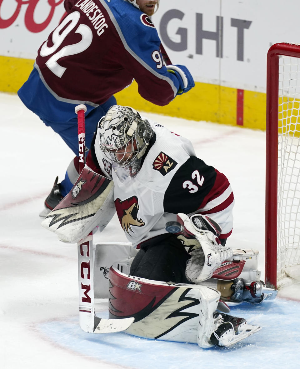Arizona Coyotes goaltender Antti Raanta, front, makes a glove-save of a shot in the third period of an NHL hockey game against the Colorado Avalanche Monday, March 8, 2021, in Denver. (AP Photo/David Zalubowski)
