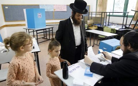 Children accompany an ultra-Orthodox Jewish man to a voting station in the city of Bnei Brak during the Israeli parliamentary election - Credit: MENAHEM KAHANA/AFP