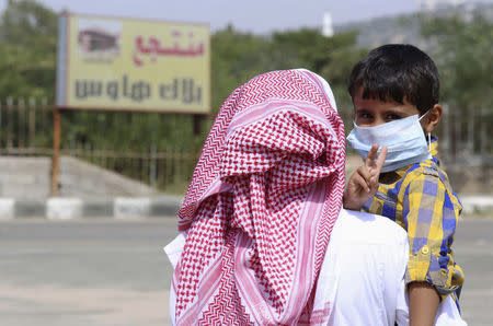 A boy wearing a mask is held by his father in Taif June 7, 2014. REUTERS/Mohamed Alhwaity