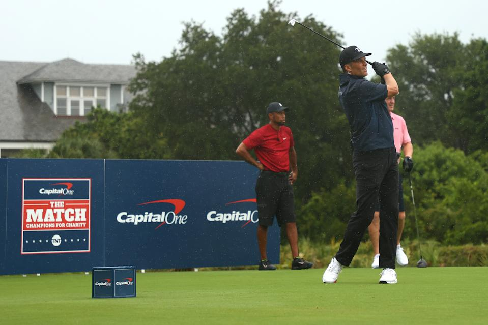 """Tampa Bay Buccaneers quarterback Tom Brady hits a shot as Tiger Woods looks on during """"The Match: Champions For Charity"""" on Sunday in Hobe Sound, Florida. (Photo by Mike Ehrmann/Getty Images for The Match)"""