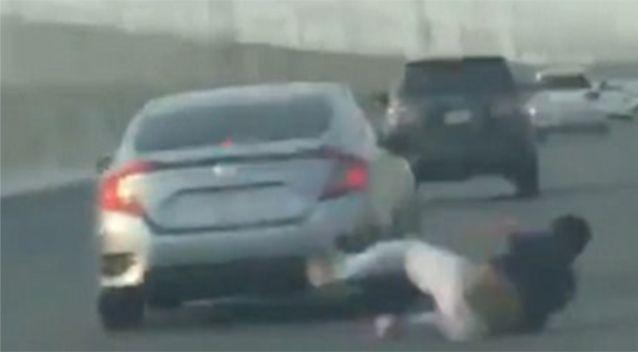 He falls out of the car onto the busy highway. Source: LiveLeak