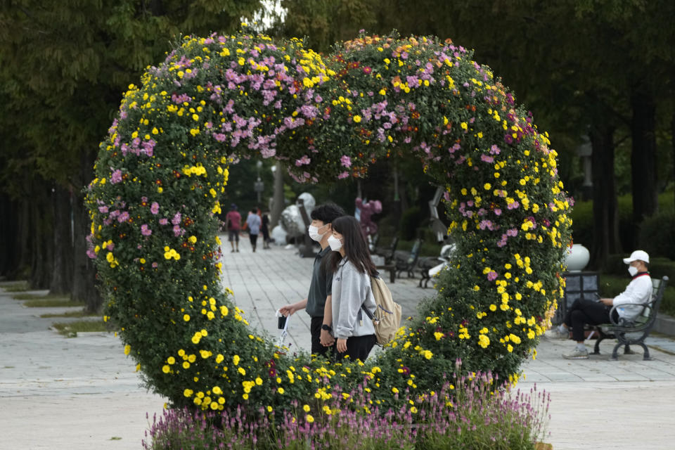 A couple wearing face masks as a precaution against the coronavirus passes by a heart-shaped chrysanthemum flower arrangement at a park in Goyang, South Korea, Tuesday, Oct. 5, 2021. (AP Photo/Ahn Young-joon)