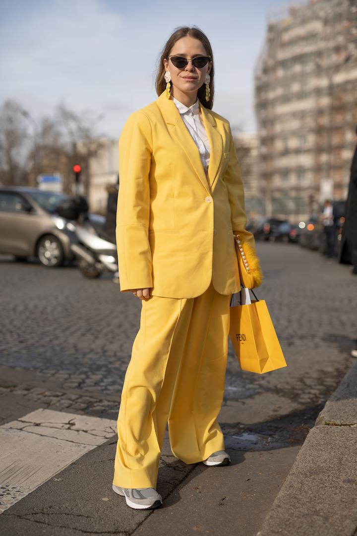 <p>A guest spotted arriving at the Lacoste show in a sunny yellow co-ord with matching earrings and 'dad' trainers. <em>[Photo: Getty]</em> </p>