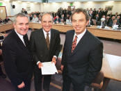 """FILE - In this April 10, 1998, file photo, from right, British Prime Minister Tony Blair, U.S. Sen. George Mitchell, and Irish Prime Minister Bertie Ahern, pose together after they signed the Good Friday Agreement for peace in Northern Ireland. The chaotic scenes during a week of violence on the streets of Northern Ireland have stirred memories of decades of Catholic-Protestant conflict, known as """"The Troubles."""" A 1998 peace deal ended large-scale violence but did not resolve Northern Ireland's deep-rooted tensions. (AP Photo/File)"""