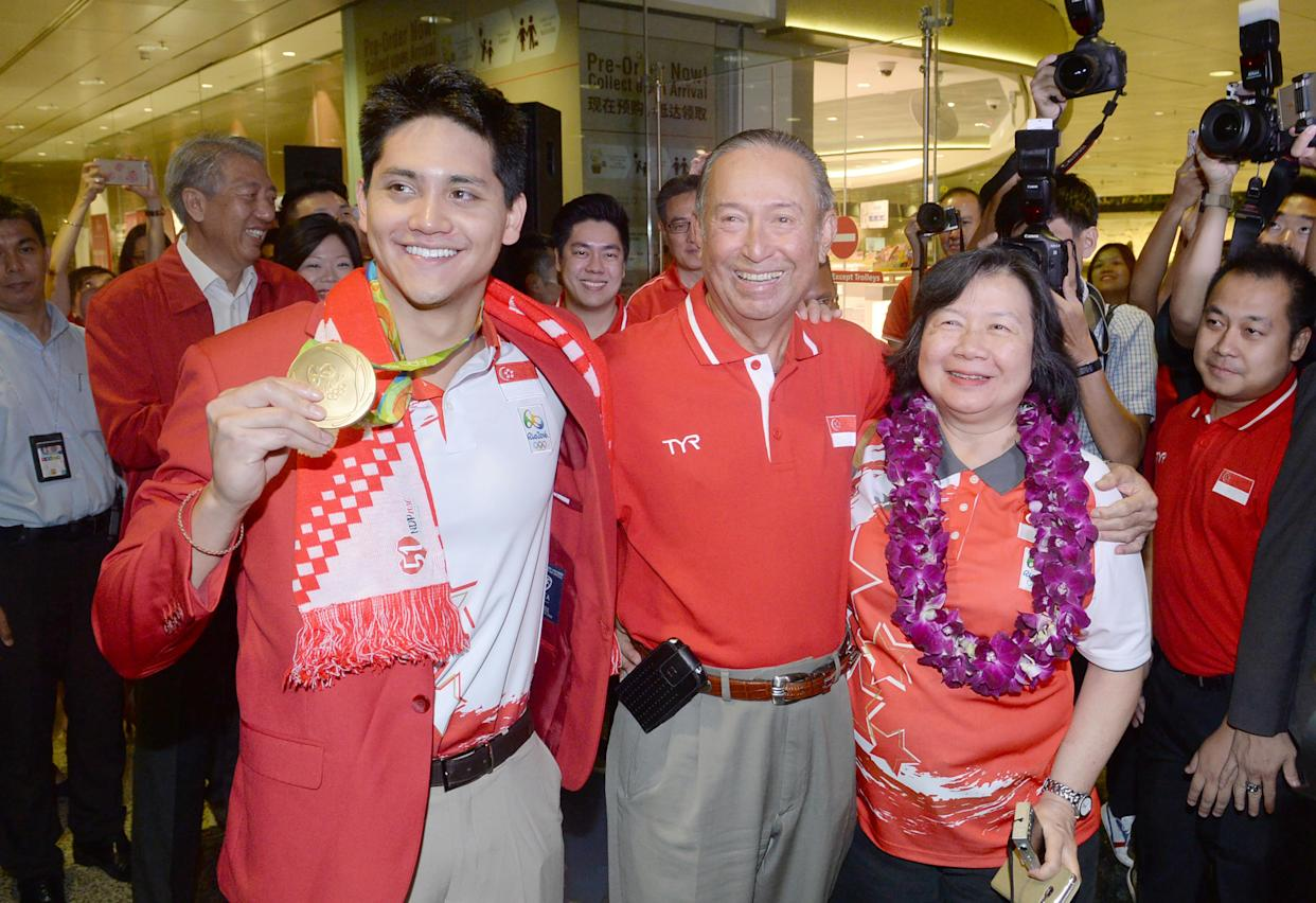 Singaporean swimmer Joseph Schooling (L) poses with his father Colin and mother May after his arrival from Rio 2016 Olympic Games on August 15, 2016 at Changi International airport in Singapore. Singapore homegrown swimming hero Joseph Schooling beat US legend Michael Phelps in the 100m butterfly in Rio to win the tiny republic's first ever Olympic gold. / AFP / ROSLAN RAHMAN        (Photo credit should read ROSLAN RAHMAN/AFP via Getty Images)