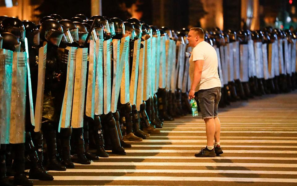 A protester speaks to police as they block the road during a rally - AP