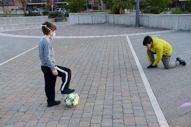 Child wearing a protective face mask against the coronavirus at the park while playing football in Rome, Italy. (PA)
