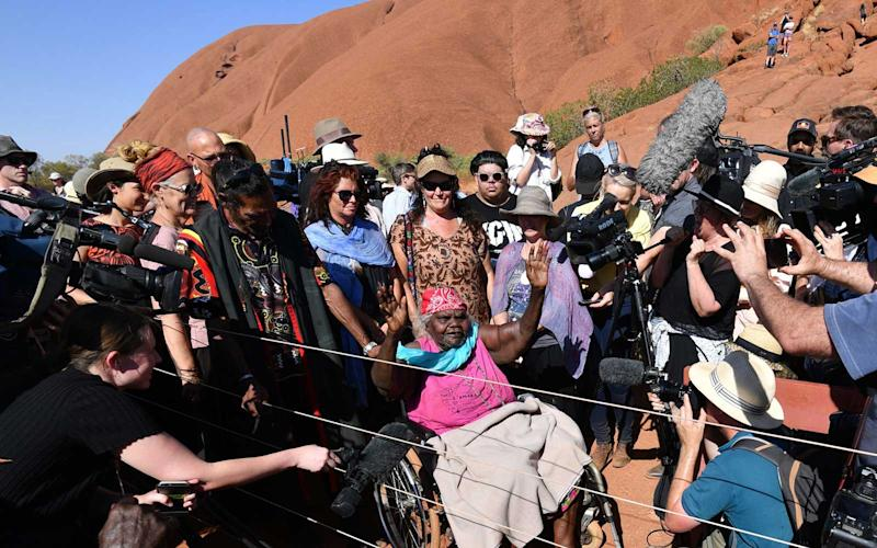 An aboriginal elder gestures while surrounded by journalists at the base of Uluru, also known as Ayers Rock, ahead of the day's end marking the start of a permanent ban on climbing the monolith, at Uluru-Kata Tjuta National Park in Australia's Northern Territory on October 25, 2019. | SAEED KHAN/Getty Images