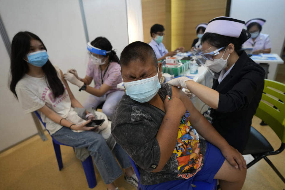 Health workers administer doses of the Pfizer-BioNTech COVID-19 vaccine at a hospital in Bangkok, Thailand, Tuesday, Sept. 21, 2021. Bangkok Metropolitan Administration inoculated 12-18 year old students Tuesday as part of its attempt to reopen on-site schools. (AP Photo/Sakchai Lalit)