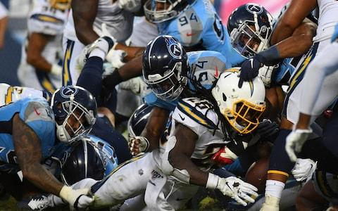 Los Angeles Chargers running back Melvin Gordon (25) is stopped short of the goal line by Tennessee Titans inside linebacker Rashaan Evans (54) during the second half at Nissan Stadium - Credit: USA Today