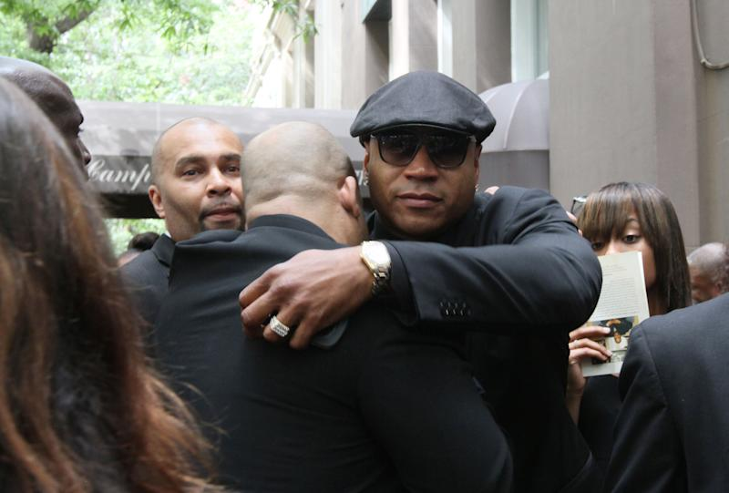 "LL Cool J, foreground right, shares an embrace with another as he leaves the Frank E. Campbell Funeral Chapel following the service for hip-hop mogul Chris Lighty, Wednesday Sept. 5, 2012 in New York.  Mourners in the packed chapel Wednesday included Sean ""Diddy"" Combs, Missy Elliott, Q-Tip, LL Cool J, Russell Simmons, 50 Cent and Grandmaster Flash. Lighty, the 44-year-old hip-hop mogul was found dead in his Bronx apartment last week with a gunshot wound to the head.  (AP Photo/Tina Fineberg)"