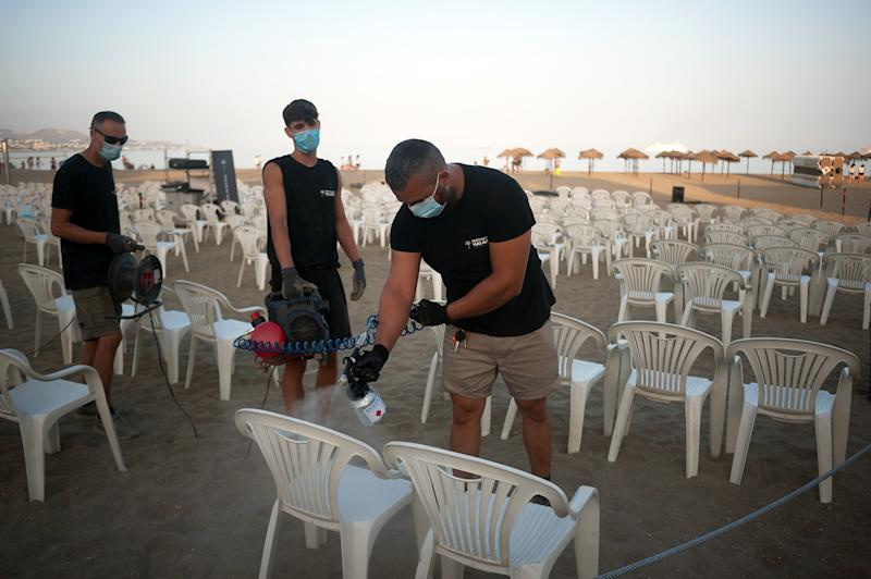 Workers are seen disinfecting chairs before the movie at La Malagueta beach amid coronavirus (COVID-19) outbreaks. During the summer season, the event 'Open cinema' welcomes free screenings of movies from 2 July until 20 August in different outdoors places like beaches, parks or district zones as people enjoy free films on this occasions, this places have to adapt safety and health measures to prevent the spread of coronavirus pandemic. (Photo by Jesus Merida / SOPA Images/Sipa USA)
