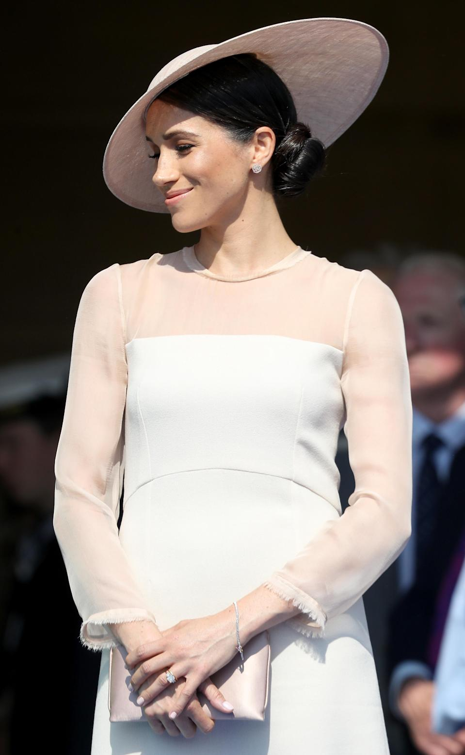 <p>For her first royal enagement since getting married, the Duchess went demure in a pale pink dress by Goat which actually caused the brand's website to crash. She paired the dress with a custom Philip Treacy hat, nude tights, the Oyster Silk Clutch by Wilbur and Gussie and matching peach-hued Aquzzara pumps. Some said Meghan's far more polished look (and hello: <em>tights</em>) singalled her newfound royal status. <em>[Photo: Getty]</em> </p>