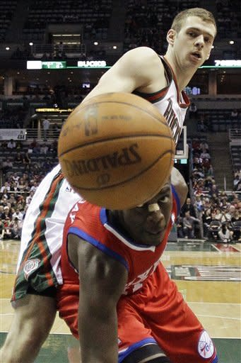 Philadelphia 76ers' Jrue Holiday and Milwaukee Bucks' Jon Leuer go after a loose ball during the first half of an NBA basketball game, Wednesday, April 25, 2012, in Milwaukee. (AP Photo/Morry Gash)