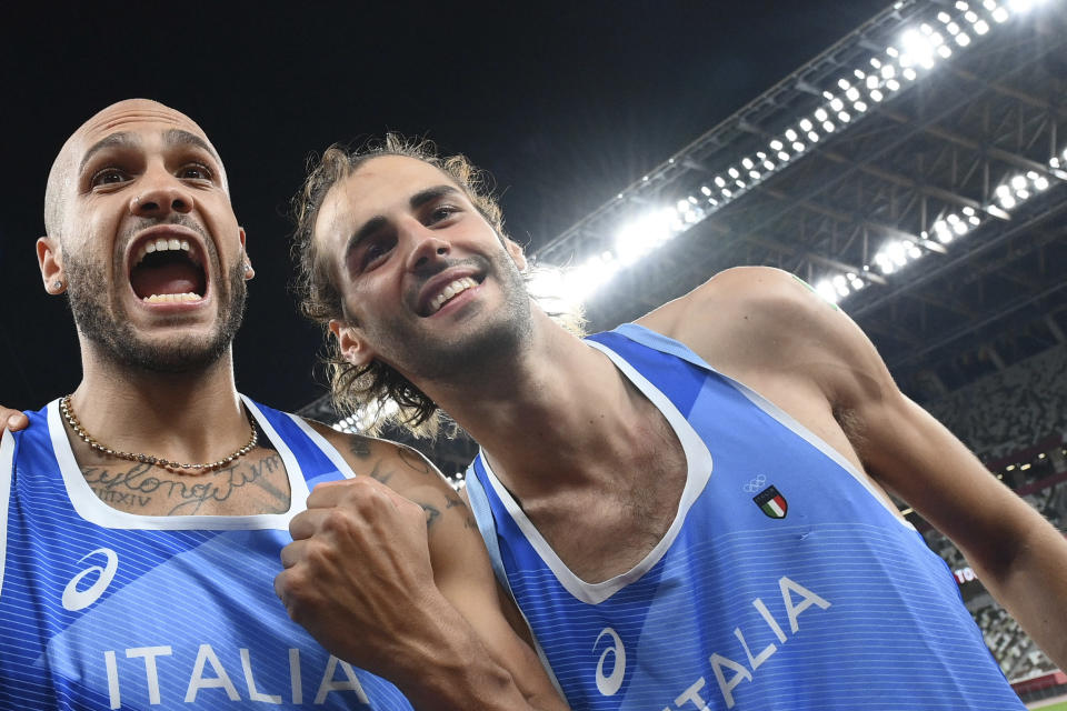 High jump gold medalist Gianmarco Tamberi, right, of Italy, celebrates with compatriot Lamont Marcell Jacobs, after he won the final of the men's 100-meters at the 2020 Summer Olympics, Sunday, Aug. 1, 2021, in Tokyo. (Alfredo Falcone/LaPresse via AP)