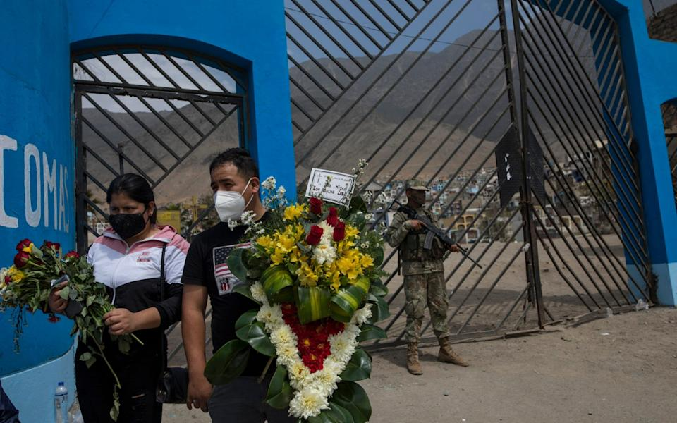 """Relatives of Eugenia Villogas, 77, who died from Covid-19, carry flowers for her burial as soldiers stands guard in the main entrance of the """"Martires 19 de Julio"""" cemetery in Comas - Rodrigo Abd/AP"""