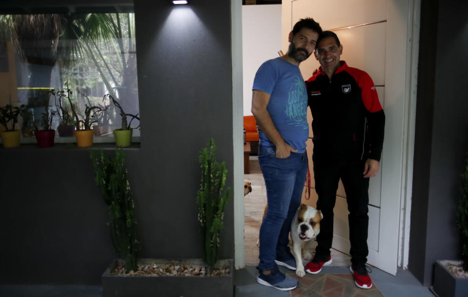 Former Catholic Priest Andres Gioeni, right, poses for a photo with his husband Luis Iarocci and their dog Boris after they got home from the bishopric where he started the process of apostasy in Buenos Aires, Argentina, Wednesday, March 17, 2021. Gioeni, who left the priesthood 20 years ago and married in 2014, said he has decided to formally leave the church after the Vatican decreed that the Catholic Church cannot bless same-sex unions since God 'cannot bless sin.' (AP Photo/Natacha Pisarenko)
