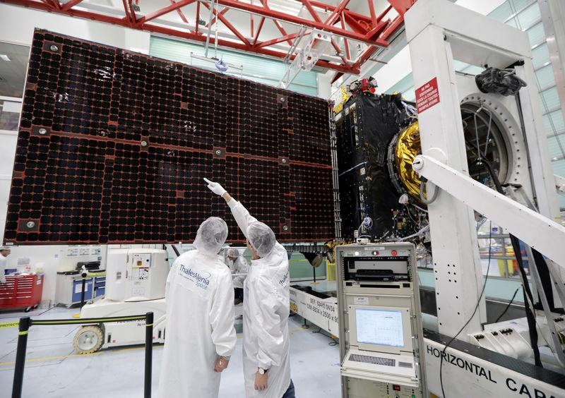 FILE PHOTO: A technician looks at a solar panel on an Inmarsat satellite in a clean room at the Thales Alenia Space plant in Cannes