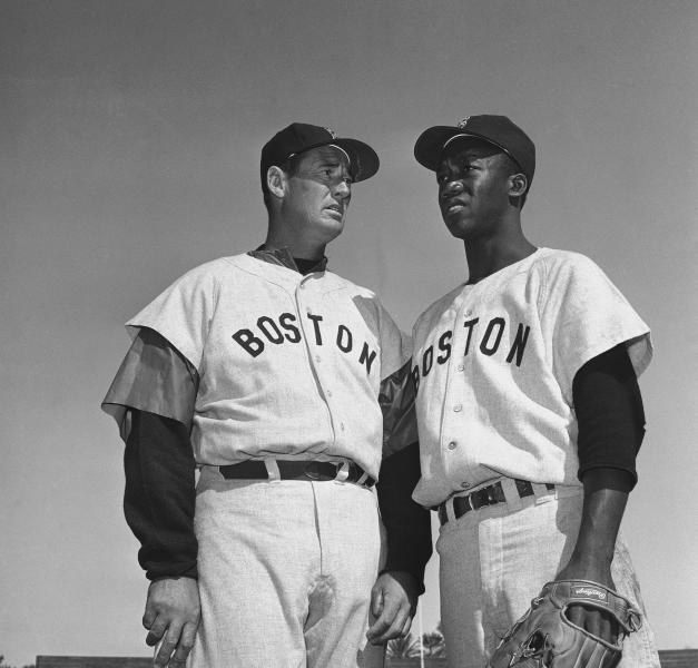 """FILE - In this March 4, 1959, file photo, Ted Williams, long-time Red Sox batting ace, chats with E.J. (Pumpsie) Green at the Boston training camp in Scottsdale, Ariz. A new film explores the life of baseball legend Williams who struggled with his Mexican-American heritage and his volatile relationship with his family and the press. The upcoming PBS """"American Masters"""" documentary on the former Boston Red Sox slugger uses rare footage and family interviews to paint a picture of a complicated figure that hid his past but later spoke out and defended black players. (AP Photo/Harold Filan, File)"""