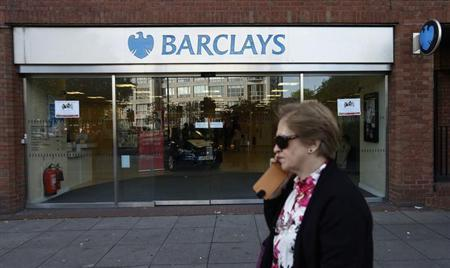 A woman walks past the Swiss Cottage branch of Barclays bank in London September 20, 2013.