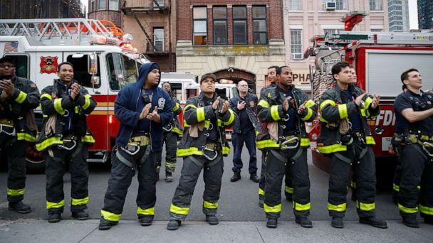 PHOTO: FDNY firefighters gather to applaud medical workers at 7pm outside Brooklyn Hospital Center, April 14, 2020, in New York. (John Minchillo/AP)