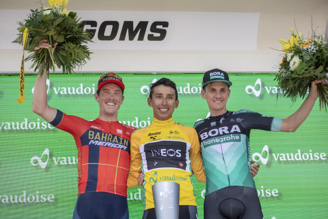 Egan Bernal from Colombia of Team Ineos, center, celebrates with Rohan Dennis from Australia of Bahrain-Merica Pro Cycling Team, left, and Patrick Konrad from Austria of Bora-Hansgrohe after winning the Tour de Suisse at the ninth and final stage, a 101.5 km race with start and finish in Goms, Switzerland, at the 83rd Tour de Suisse UCI ProTour cycling race, on Sunday, June 23, 2019. (Urs Flueeler/Keystone via AP)