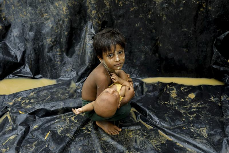 A Rohingya child holds a baby after arriving at a refugee camp near Teknaf, Bangladesh, on Sept. 5, 2017. (K M ASAD via Getty Images)