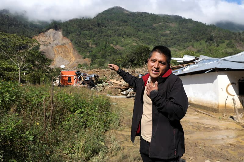 Rolando Cal, who lost 23 relatives, including his wife and sons, during a mudslide caused by heavy rains brought by Storm Eta, gestures while looking for help to look for their loved ones, in the buried village of Queja