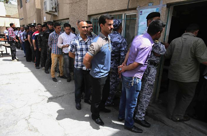 Iraqi security forces queue to vote outside a polling center in Baghdad, Iraq, Monday, April 28, 2014. As parliamentary elections are held Wednesday, more than two years after the withdrawal of U.S. troops, Baghdad is once again a city gripped by fear and scarred by violence. (AP Photo/ Karim Kadim)
