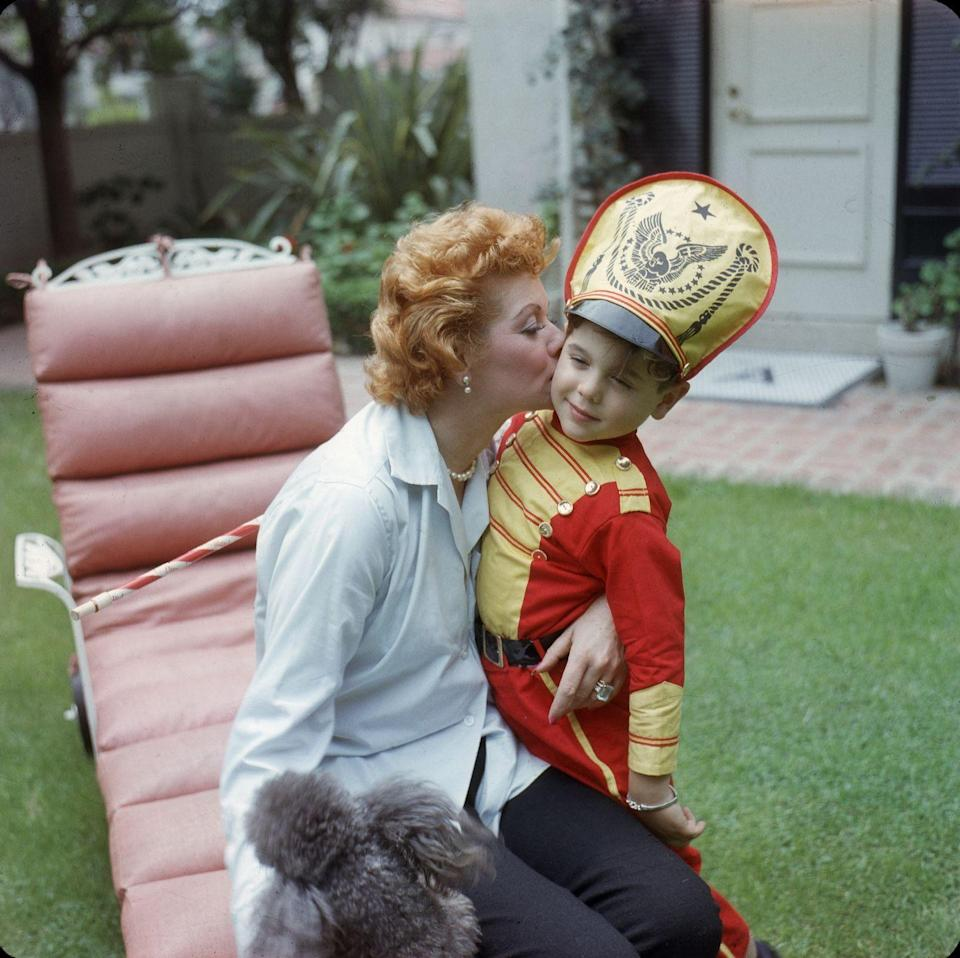 <p>Lucille plants a massive kiss on her son Desi Arnaz, Jr.'s cheek in 1957. The comedian and actress was spending time with her youngest in the backyard of their Beverly Hills home in 1957. </p>