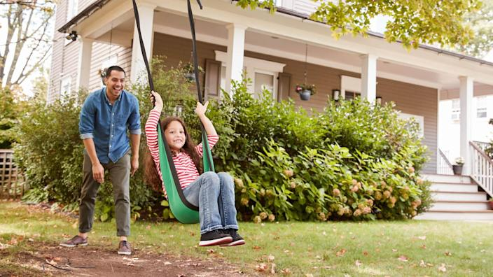 Father Pushing Daughter On Garden Swing At Home.