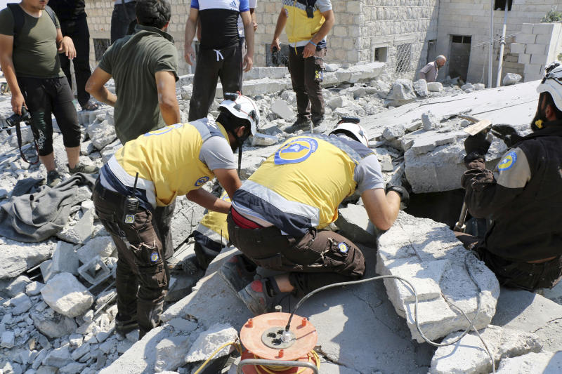 This photo provided by the Syrian Civil Defense White Helmets, which has been authenticated based on its contents and other AP reporting, shows Syrian White Helmet civil defense workers search for victims from under the rubble of a destroyed building that hit by airstrikes, in Deir al-Sharqi village, in Idlib province, Syria, Saturday, Aug 17, 2019. Syrian activists and a war monitor say airstrikes have pounded the southern edge of a rebel stronghold in the country's northwest, in one instance killing seven including children. (Syrian Civil Defense White Helmets via AP)