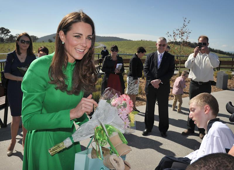 Britain's Catherine, Duchess of Cambridge (L), receives gifts for her son Prince George while visiting the National Arboretum in Canberra on April 24, 2014. Britain's Prince William, his wife Kate and their son Prince George are on a three-week tour of New Zealand and Australia. AFP PHOTO / Mark GRAHAM (Photo credit should read MARK GRAHAM/AFP via Getty Images)