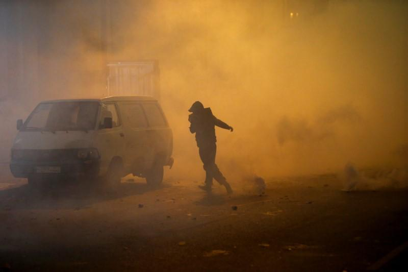 A demonstrator runs as the smoke rises during a protest against a ruling elite accused of steering Lebanon towards economic crisis in Beirut