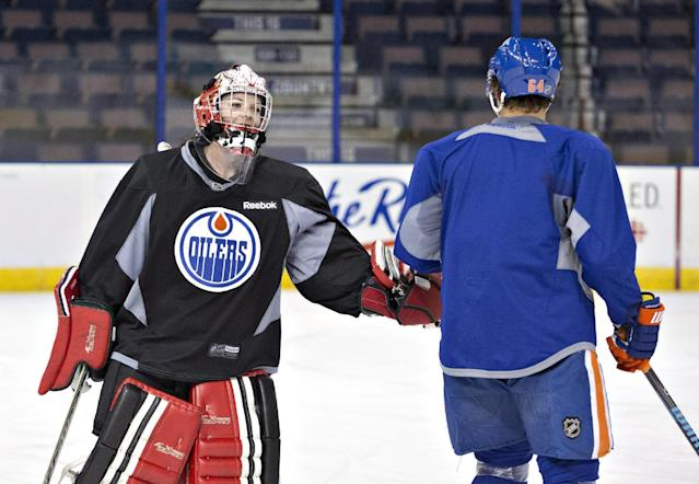 Canadian Olympic women's team goalie Shannon Szabados gives a low-five to Nail Yakupov during practice with the Edmonton Oilers NHL hockey team in Edmonton, Alberta, Wednesday, March 5, 2014. (AP Photo/The Canadian Press, Jason Franson)