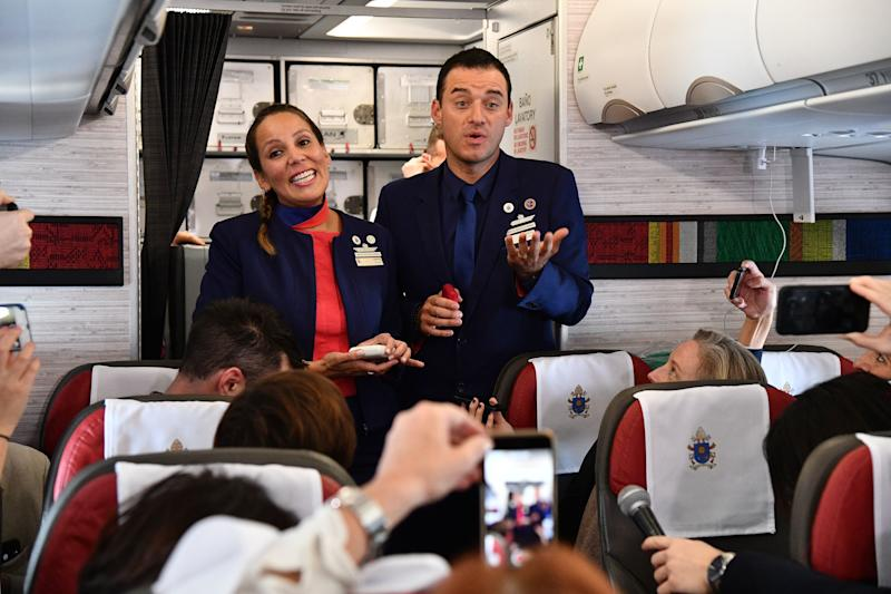 The newly married coupletalk toreporters on the plane moments after being married by Pope Francis. (VINCENZO PINTO via Getty Images)