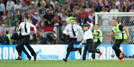 FILE PHOTO: Soccer Football - World Cup - Final - France v Croatia - Luzhniki Stadium, Moscow, Russia - July 15, 2018 Stewards chase pitch invaders REUTERS/Carl Recine