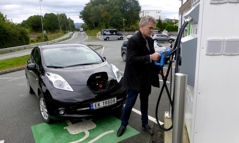 A man recharges his Nissan Leaf electric car in Finnøy, Norway.