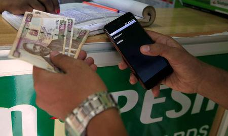 Customer conducts a mobile money transfer at a Safaricom agent stall in Nairobi