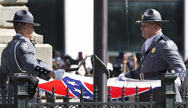<p>An honor guard from the South Carolina Highway Patrol lowers the Confederate battle flag as it is removed from the Capitol grounds, Friday, July 10, 2015, in Columbia, S.C. The move was a stunning political reversal in a state where many thought the rebel banner would fly indefinitely. (Photo: John Bazemore/AP) </p>