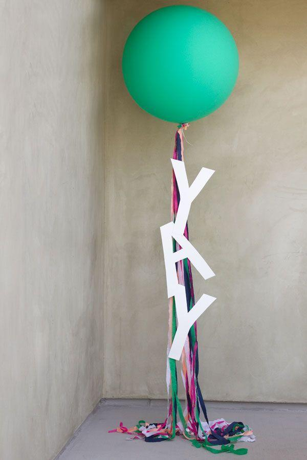 """<p>Give your balloon strings a makeover by adding streamers and poster board letters to spell out a celebratory message. </p><p><strong><em><a href=""""https://studiodiy.com/diy-giant-balloon-messages/"""" rel=""""nofollow noopener"""" target=""""_blank"""" data-ylk=""""slk:Get the tutorial at Studio DIY"""" class=""""link rapid-noclick-resp"""">Get the tutorial at Studio DIY</a>. </em></strong></p><p><a class=""""link rapid-noclick-resp"""" href=""""https://www.amazon.com/Staples-White-Poster-Boards-10-Pack/dp/B00WKZPALM?tag=syn-yahoo-20&ascsubtag=%5Bartid%7C10070.g.37055923%5Bsrc%7Cyahoo-us"""" rel=""""nofollow noopener"""" target=""""_blank"""" data-ylk=""""slk:SHOP POSTER BOARD"""">SHOP POSTER BOARD</a></p>"""