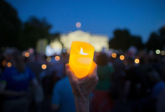 "<p>People hold up lights and candles during a national vigil ""to demand democracy"" and ""confront corruption"" on Pennsylvania Avenue outside the White House in Washington, D.C., on July 18, 2018. Vigils were organized at various locations throughout the U.S. to criticize President Trump for his handling of a news conference with Russian President Vladimir Putin in Helsinki on July 16, 2018. (Photo: MICHAEL REYNOLDS/EPA-EFE/REX/Shutterstock) </p>"