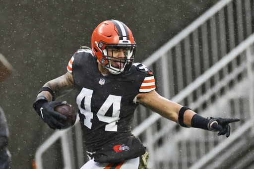 Cleveland Browns linebacker Sione Takitaki looks back as he runs for a 50-yard interception return touchdown during the first half of an NFL football game against the Philadelphia Eagles, Sunday, Nov. 22, 2020, in Cleveland. (AP Photo/Ron Schwane)