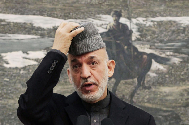 Afghan President Hamid Karzai adjusts his hat as he speaks during a press conference at the presidential palace in Kabul, Afghanistan, Monday, Jan. 14, 2013.  Karzai says a national meeting of elders should be called to decide whether U.S. troops staying in Afghanistan after 2014 would be immune from prosecution under Afghan law. (AP Photo/Ahmad Jamshid)