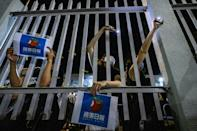 Supporters stand outside the main gate of the Apple Daily offices after the company's final newspapers were printed early on June 24, 2021