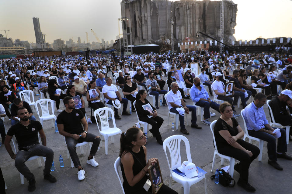Relatives of victims who were killed in the massive blast last year at the Beirut port holds their portraits as they attend a Mass held to commemorate the first year anniversary of the deadly blast, at the Beirut port, Lebanon, Wednesday, Aug. 4, 2021. (AP Photo/Hussein Malla)