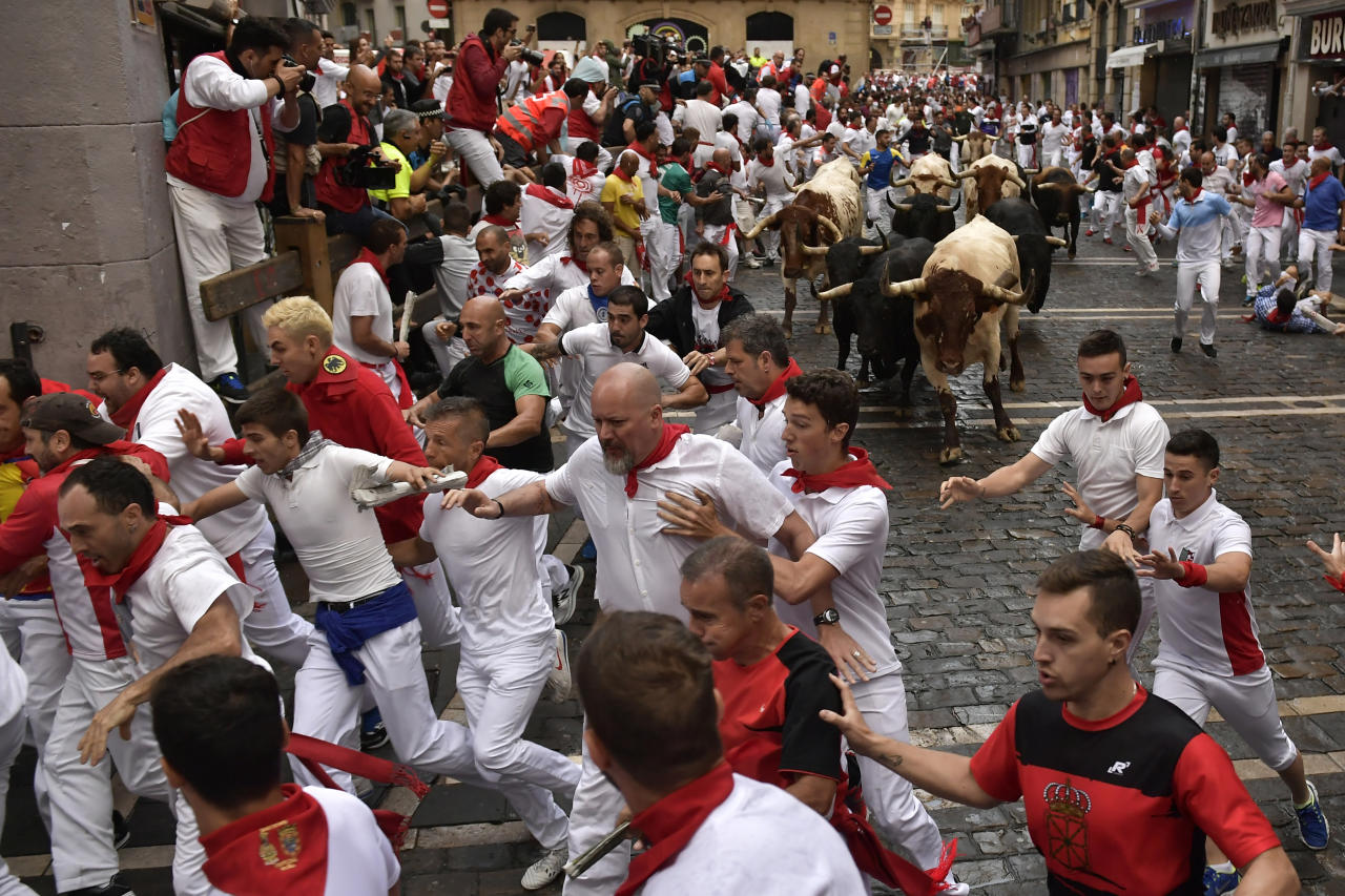 <p>Revellers run next to fighting bulls from the Victoriano del Rio ranch during the 6th day of the running of the bulls at the San Fermin Festival in Pamplona, northern Spain, July 12, 2018. (Photo: Alvaro Barrientos/AP) </p>