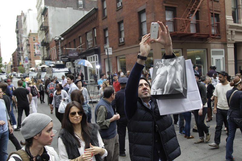 Tourists take photos of the scene outside the building on the corner of Wooster Street and Prince Street in the Manhattan borough of New York on Friday, April 20, 2012 during a renewed investigation into the 1979 disappearance of 6-year-old EtanPatz. Patz vanished after leaving his family's home for a short walk to his school bus stop. NYPD spokesperson Paul Browne says the building being searched for his remains is about a block from where the family lived. (AP Photo/Mary Altaffer)