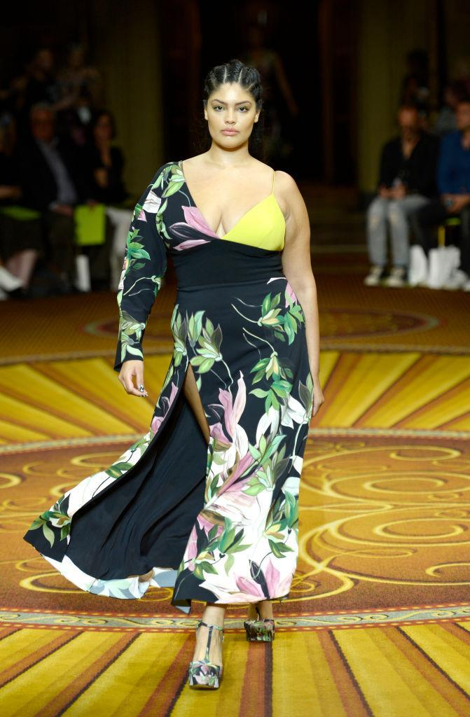 <p>A curvy model walks Christian Siriano's runway wearing an asymmetrical floral, high-slit dress during New York Fashion Week. (Photo: Getty Images) </p>