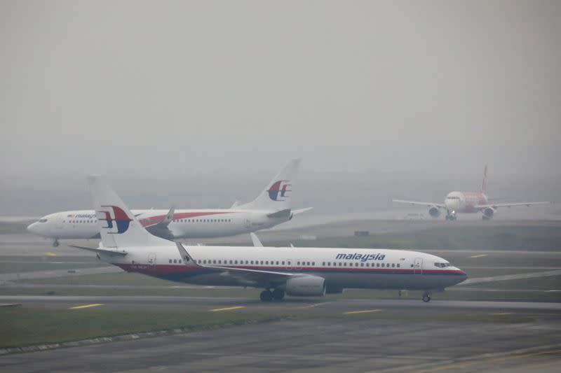 FILE PHOTO: Malaysia Airlines airplanes are pictured on the haze-shrouded tarmac at Kuala Lumpur International Airport in Sepang